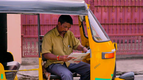 A rickshaw driver reading a newspaper inside auto rickshaw in india Live Action