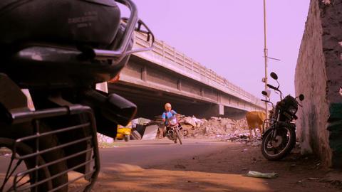 Camera low angle street scene under the bridge, black car comes towards camera Live Action