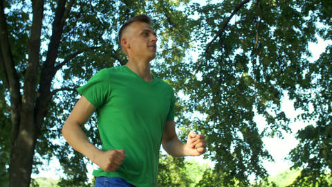 Athletic sporty young man jogging in public park Footage