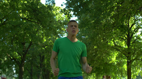 Healthy fit handsome man jogging in park Footage