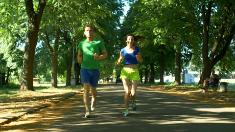 Athletic attractive couple running in public park Footage