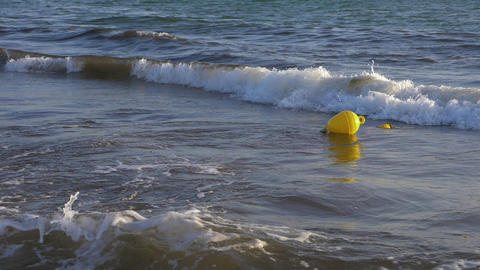 Yellow buoy floating in sea water slow motion. Sea buoy floating on water waves Archivo