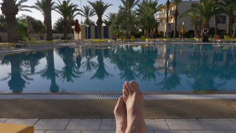 Male feet lying on deckchair front swimming pool in luxury place Archivo