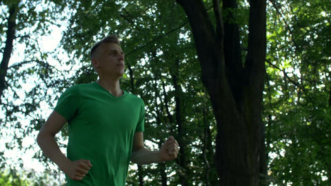 Athletic jogging handsome man running in nature Footage