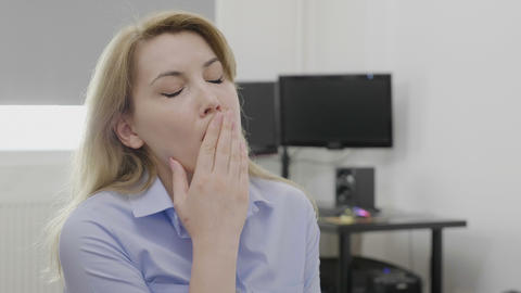Blonde young sleepy employee at office desk yawning looking bored and tired Footage