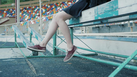 the legs of a woman are hanging at the football stadium. feet in red sneakers ビデオ