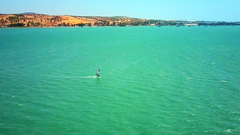 windsurfer sails in turquoise ocean at distant seashore Live Action
