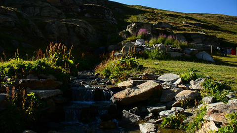 Ceresole (Torino), Italy - Sectember 5, 2012: Alps mountain stream with frozen waterfall in gran Live Action