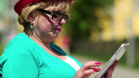 Woman with tablet computer. Woman sits on the bench and uses tablet computer Footage