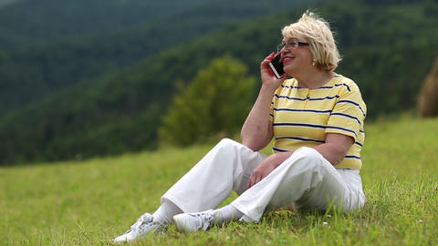 Woman sits on a green grass and talks on a cell phone Footage