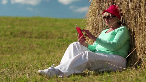 Woman sits on a green grass near haystack and uses cell phone Footage