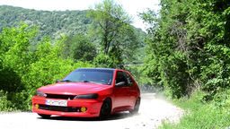 Red rally car that rushes serpentines through the forest leaving black smoke and Footage