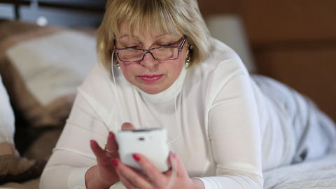 Blonde woman in glasses with white smartphone lying on the bed Footage