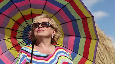 Blonde woman in glasses with brightly coloured umbrella Footage