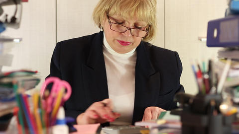 Woman bookkeeper among commercial papers, with calculator and pen Live-Action