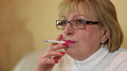 Senior woman with glasses smoking a cigarette, female smoker Live Action