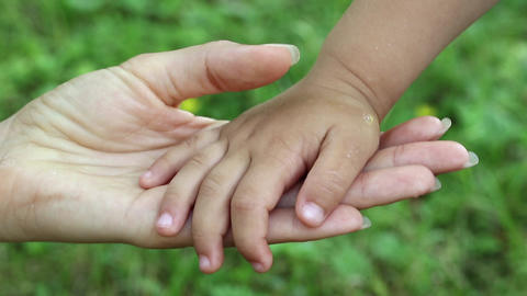 Mother and daughter hands on grass background. Hand in hand Footage