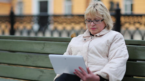 Woman sits on the bench and uses tablet computer. Woman with Tablet PC Footage