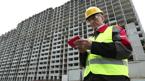 Engineer in yellow helmet stands with red smartphone near unfinished house Footage