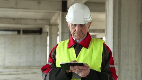 Master builder with tablet PC at construction site Footage