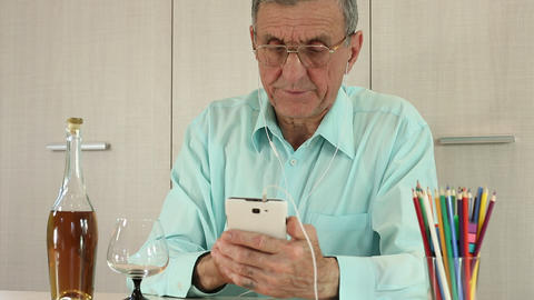 Senior man with white mobile phone and bottle of cognac sits at a table Footage