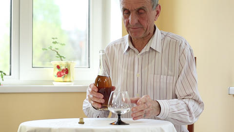 Senior man sits at the table and pours brandy in glass Footage
