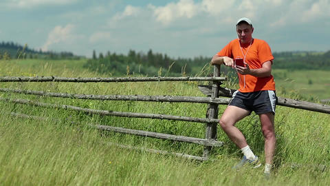 Man in orange t-shirt stands in field and communicate via smartphone Footage