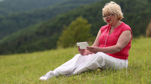 Blond woman sits in the meadow on green grass and talks via skype Footage