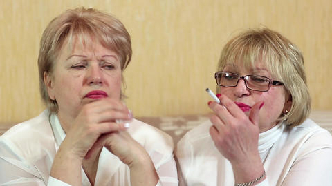 Two women sits on a couch and one woman smokes a cigarette Footage