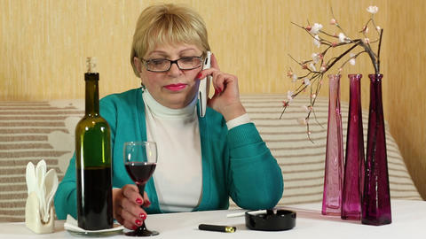 Woman sits at the table, drinks red wine and talks on smartphone Footage
