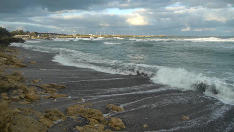 Sea waves that break the rocky shore, leading them to a beach sand near the port Footage