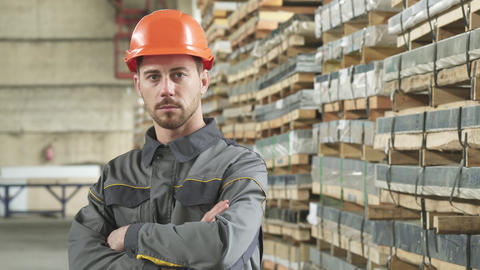Portrait of a handsome serious metalworker posing at the factory storage Live Action
