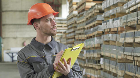 Warehouse worker writing on his clipboard standing at the storage Footage