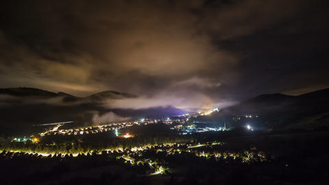 Epic clouds moving over village lighting at starry night Time lapse Footage
