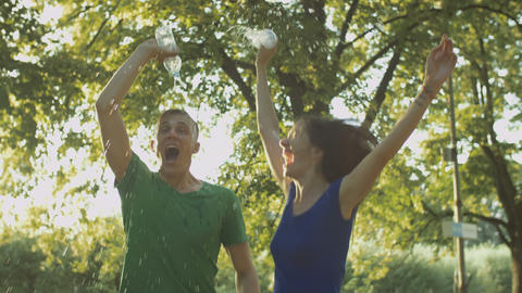 Excited couple runners pouring water over themselves Footage