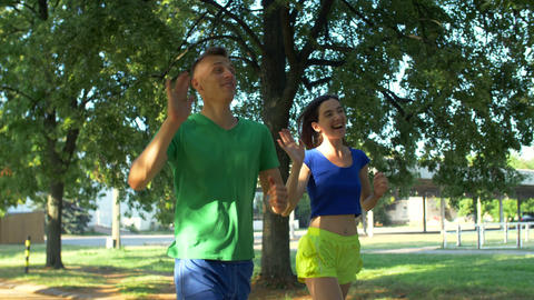 Healthy active couple runners meeting friends in park Footage