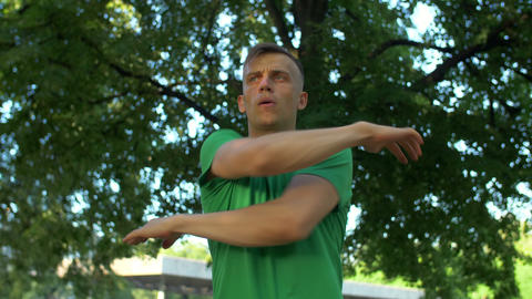 Healthy athletic man stretching arms and neck in park Footage