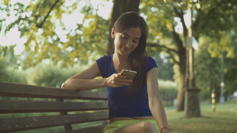Smiling pretty woman texting on cellphone in park Footage
