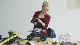 Woman playing with radio-controlled car in workshop Archivo