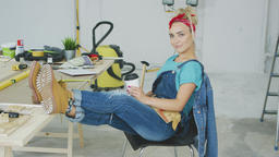 Female relaxing at carpenter workbench with drink ビデオ