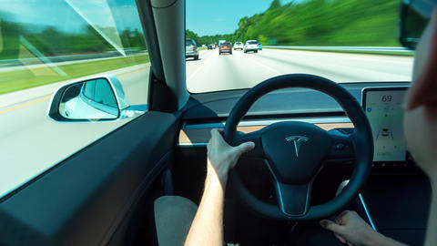 Person driving a new Tesla Model 3 in autopilot. The model 3 is set to be the Live Action