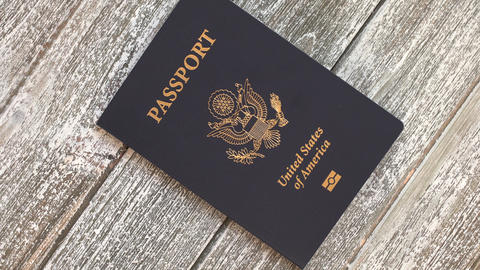 USA passport identification document book on a wooden table Live Action