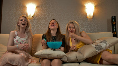 Three beautiful young and smiling girls in evening dresses watch comedy Footage