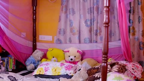 tilt down shot of bedroom with teddy bear in bed at home Footage