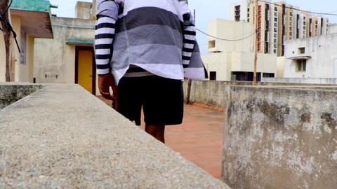 The young man walking over the top of the floor, back view shot of young boy Live Action