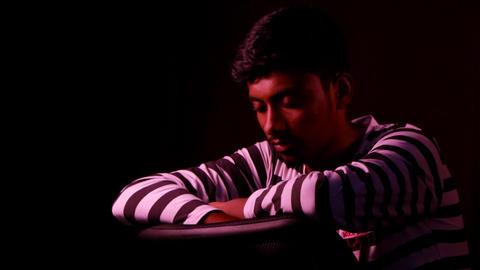 Depressed man sitting in dark empty room Footage