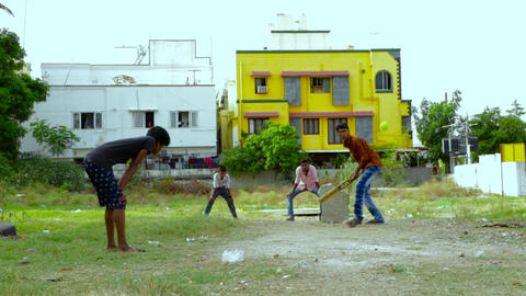 Teenage boys playing casual game of cricket using tennis ball Footage