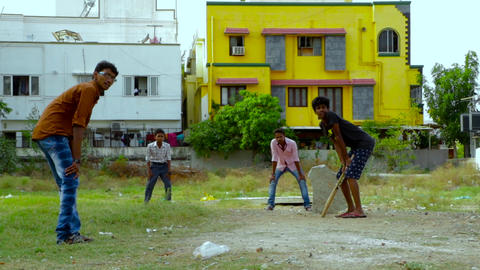 young boys playing cricket in a park Footage
