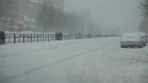 Snow-covered city road with cars in the snow Footage