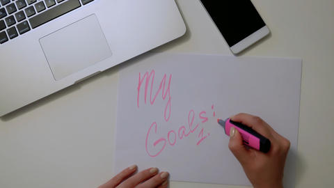 Woman writes new goals on white paper. Good motivation Fotografía